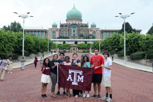 Texas A&M students holding Texas A&M flag in front of building in Malaysia